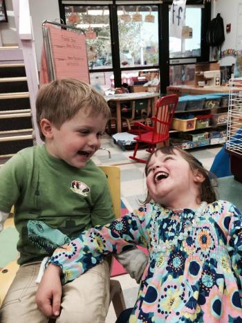 Honors program staff member Amanda Bennett's two children laugh in the child development center