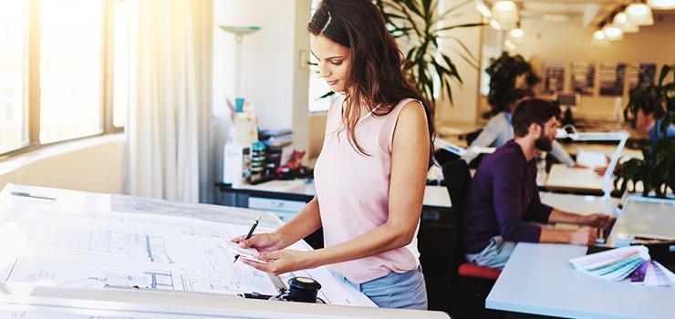 woman lookover blueprints near the window