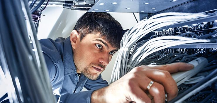 network specialist uses an insertion tool to snap wires into place